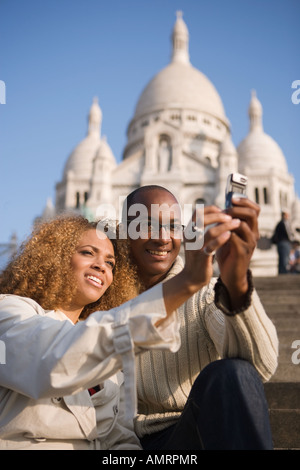 African couple taking own photograph - Stock Photo