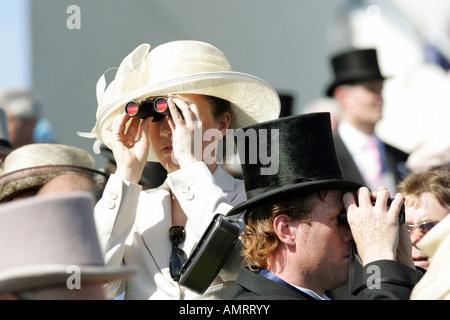 People looking through binoculars at horse races in Epsom, Great Britain - Stock Photo