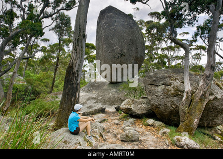 A young woman sat looking at Balancing Rock, a huge granite boulder in the ancient Porongurup National Park, Western - Stock Photo