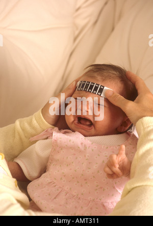 Mother taking babys temperature using a 'strip thermometer' - Stock Photo