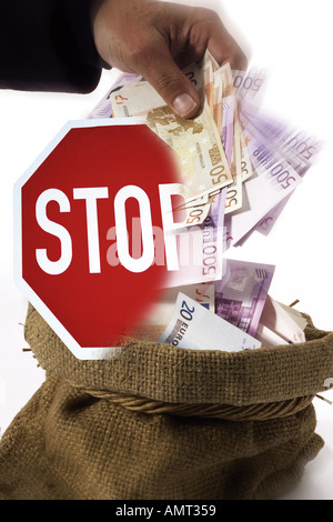 man taking money out of a sack, stop sign - Stock Photo