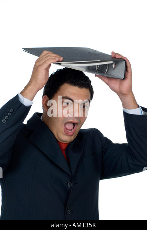 Angry employee holding binder over his head - Stock Photo