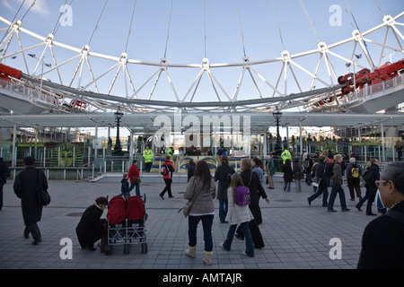 Visitors passing the base of the London Eye ferris wheel on the south bank of the River Thames. London, England. - Stock Photo