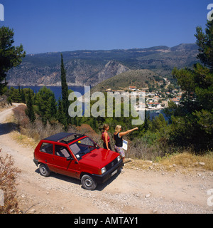 Two girls standing by red hire car reading a map and overlooking sea at Assos Cephalonia Island Ionian Islands The - Stock Photo