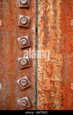 A close up of a seam on an old water tank showing the rust and fastening nuts - Stock Photo