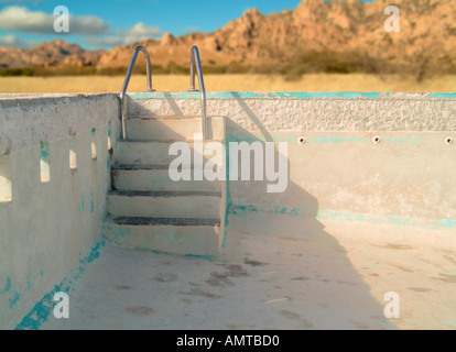 an empty concrete swimming pool with steps leading down into the pool - Stock Photo
