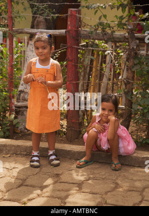 Two small pretty young girls one sitting one standing pose impishly in San Jacinto village Republic of Nicaragua - Stock Photo