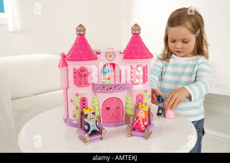 A young girl plays at a table in a sitting room with a pink toy dolls house - Stock Photo
