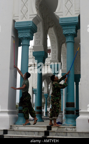 Indonesian Army works on paint after the Tsunami at the Mesijid Raya Baiturrahman Mosque in Banda Aceh Indonesia - Stock Photo