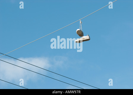 A pair of white sneakers hanging from overhead power lines after being thrown there as a teenage prank - Stock Photo