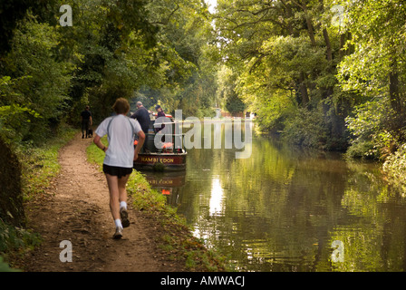 a jogger on the towpath of the canal of the Wey Navigation in Surrey UK; dog walker and canalboat - Stock Photo