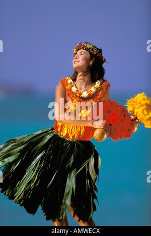 USA, Hawaiian Islands. Woman in colorful hula costume dancing on beach - Stock Photo