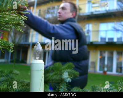 positioning of a christmas tree, candle of a fairy light at the christmas tree, Germany - Stock Photo