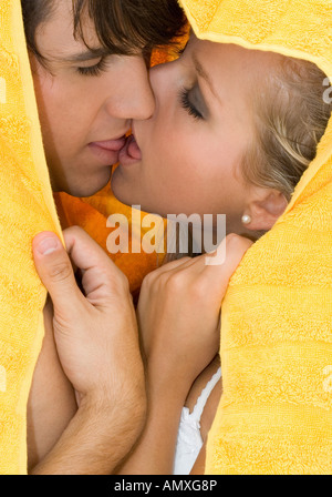 Couple kissing under a bath towel - Stock Photo