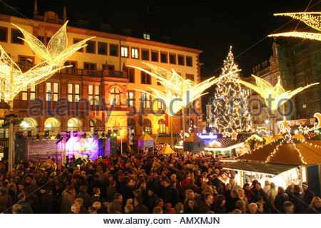 Crowd at lit up Christmas market in city Wiesbaden Germany - Stock Photo