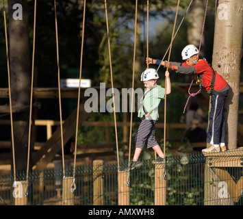 PICTURE CREDIT DOUG BLANE Young boy being helped across a log bridge at the Aerial Extreme Willen Lake Milton Keynes - Stock Photo