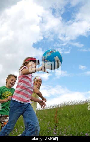 three children playing with ball in field - Stock Photo
