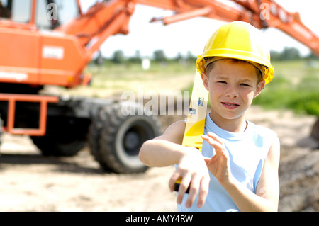 Portrait of boy wearing hardhat and holding spirit level - Stock Photo