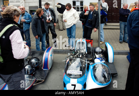 Men drinking looking at a sidecar in street - Stock Photo