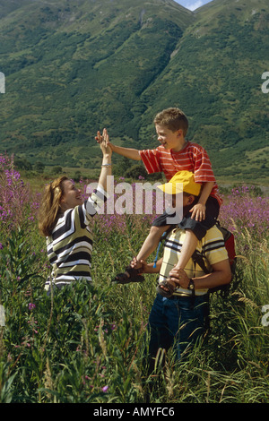 Family Hiking Meadow Together Turnagain Pass AK KP Summer - Stock Photo
