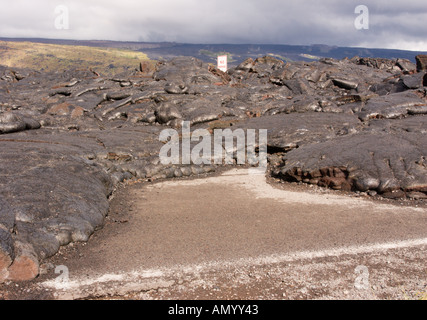 Lava flow from Kilauea Volcano solidified around No Standing traffic sign on old east coast road of Big Island Hawaii - Stock Photo
