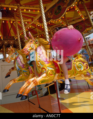 young girl holding balloon on funfair ride, norfolk, england - Stock Photo