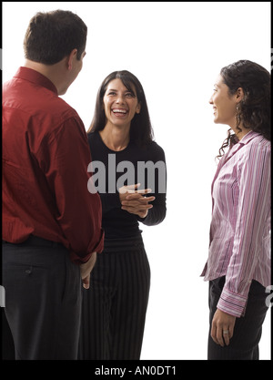 Two businesswomen and a businessman talking to each other - Stock Photo