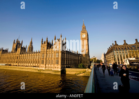 UK London commuters crossing Westminster Bridge towards Big Ben St Stephens Tower early morning - Stock Photo