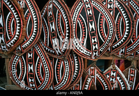Selection of Masai shields made from hide and painted with geometric motifs sold as souvenirs on a market stall - Stock Photo
