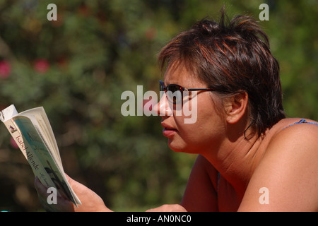 Woman on holiday reading a book in the sun - Stock Photo