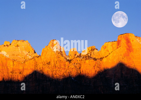 Full moon and winter dawn on the Towers of the Virgin Zion National Park Utah - Stock Photo