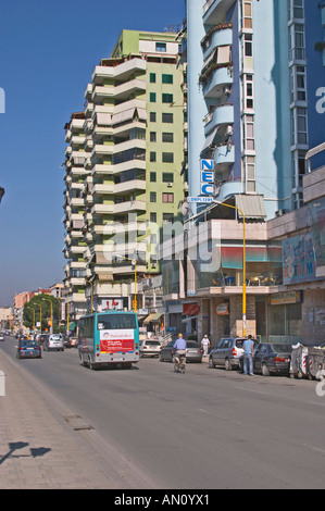 Street scene in with tall modern colourful apartment buildings a bus, people walking on the street. Tirana capital. - Stock Photo