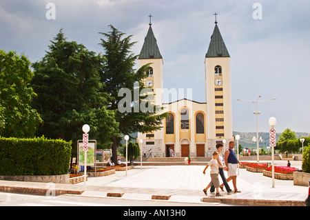 The church with its twin church towers. A family walking in front of the church. Medugorje pilgrimage village, near - Stock Photo