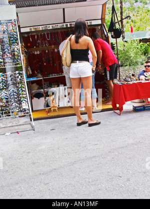 A young woman with very small tight shorts hotpants looking at a stall selling tourist souvenirs and sun glasses. - Stock Photo