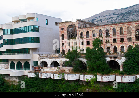Building in Mostar damaged by the war and still not renovated. Ruined by bullet holes, mortar bomb shell grenade - Stock Photo