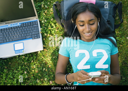 Indian female college student listening to mp3 player - Stock Photo