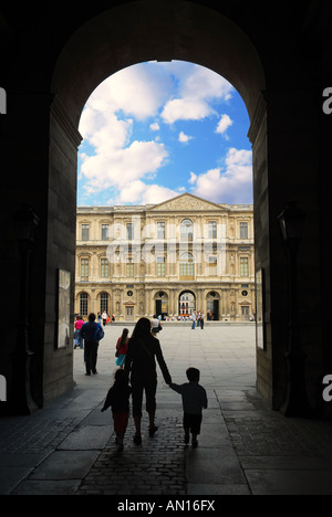 Mother and children entering Louvre in Paris France - Stock Photo