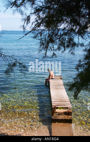 A man sitting on a wooden jetty on the stony beach looking towards the sea half hidden by pine trees. Orebic town, - Stock Photo