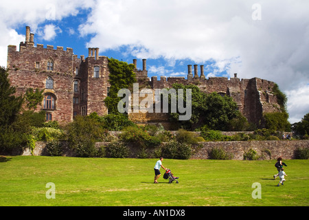 Berkeley Norman castle with young couple and pushchair in the grounds in summer Glos Gloucestershire England UK - Stock Photo
