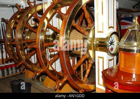 ships wheel HMS Warrior Portsmouth England UK guns in background - Stock Photo