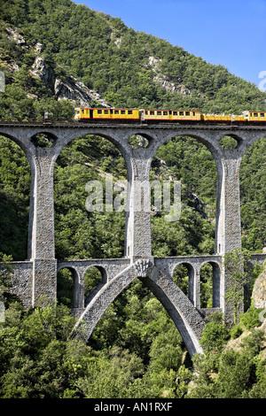 Train jaune on the Séjourné bridge, in Pyreneans mountains, Languedoc Roussillon, France. - Stock Photo