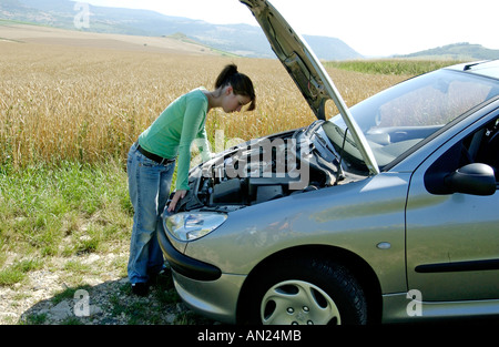 Young driver with a broken down car - Stock Photo