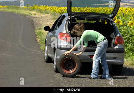 Woman changing her flat tyre - Stock Photo