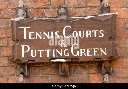 Rotten wooden wall mounted direction sign to Tennis Courts and Putting Green in Ross on Wye Herefordshire England - Stock Photo