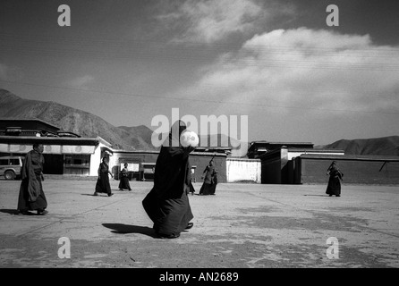 Yellow Hat sect monks playing football Xiahe Gansu Province Peoples Republic of China - Stock Photo