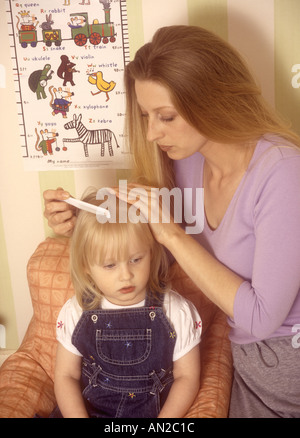 Mother checking young girls hair for head lice - Stock Photo