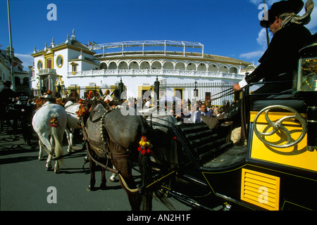 A horse drawn carriage and spectators on their way to a bullfight on the Maestranza Bullring the April Fair of Seville - Stock Photo