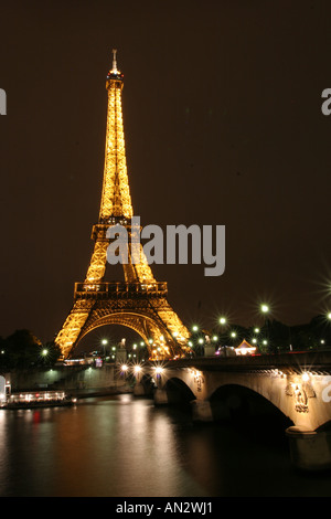 Eiffel Tower and illuminated bridge at night, Paris, France - Stock Photo