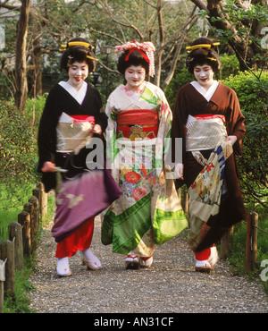 Geisha women in colorful kimonos on pathway in Tokyo park - Stock Photo