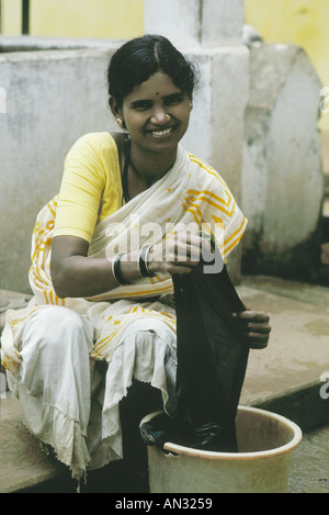 Indian woman washing clothes outside her home in a rural ...